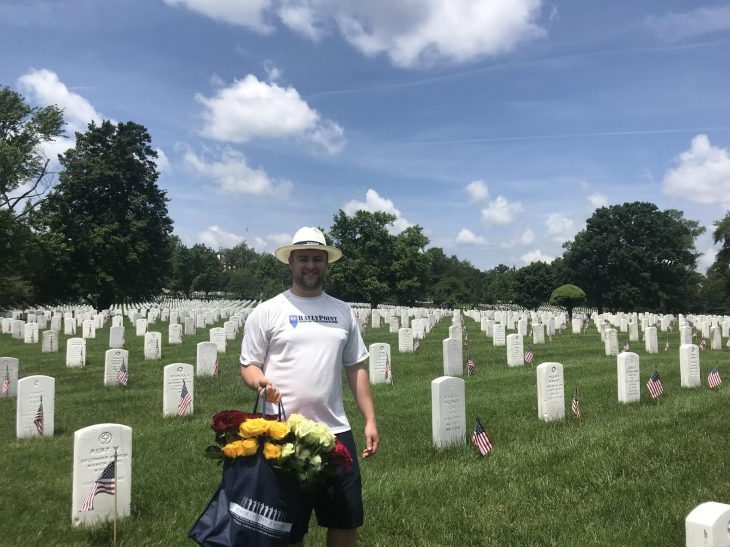 man laying flowers at graves
