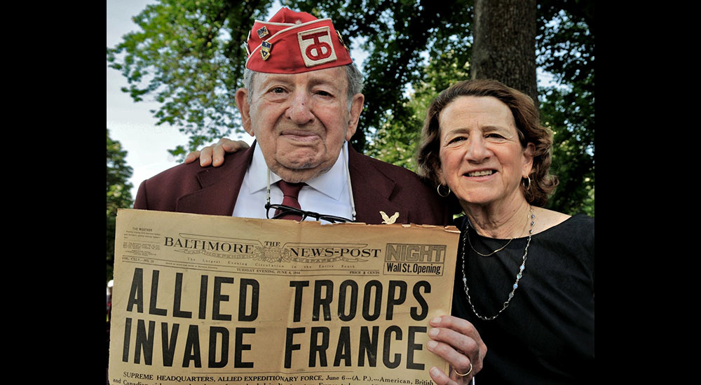 Veteran and daughter with WWII newspaper