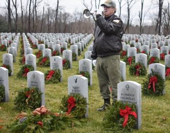 man playing bugle at cemetery