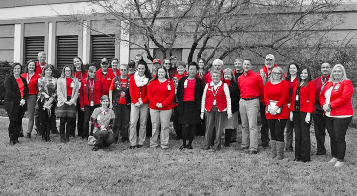 A black and white photo of a group of women, with the only color being their red shirts