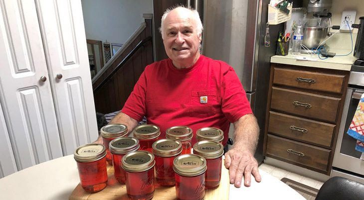 Man sitting at table with many jars of crabapple jelly