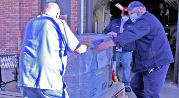 Three men loading a freezer on a pallet