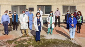 15 people wearing masks pose for photo outside hospital
