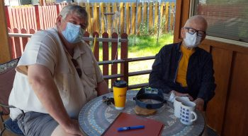 Two men, wearing masks, sitting at a table
