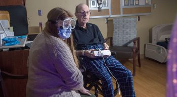 Therapist assists elderly resident with control pad