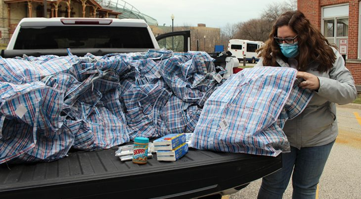 Woman collects kits for homeless from back of truck
