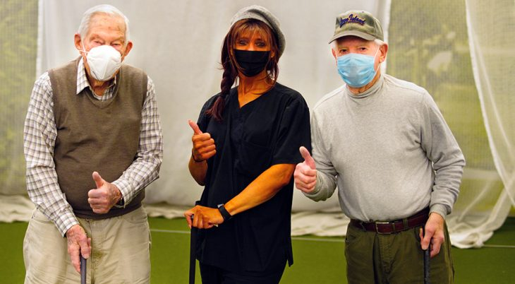 Three people wearing masks, holding golf clubs, giving thumbs up