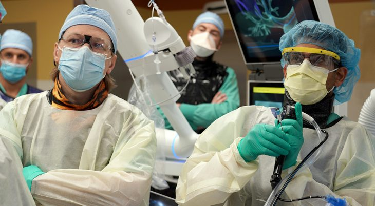 Doctor operates robotic system as others observe