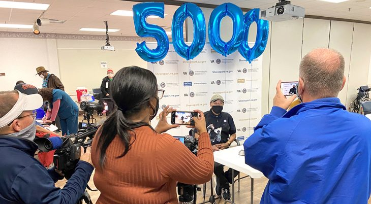 People taking pictures of man sitting under balloons saying 5000
