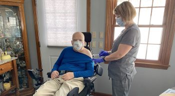 Nurse gives vaccine to man in wheelchair