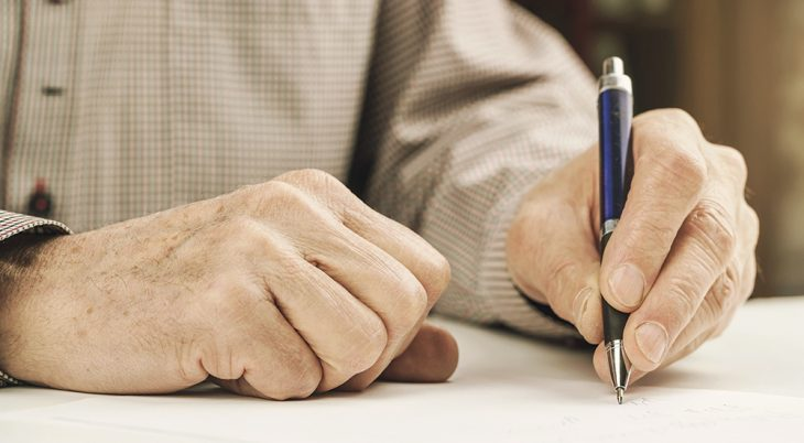 Hands holding pen and writing