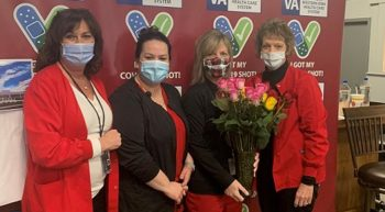 Four female nurses, wearing masks, holding roses