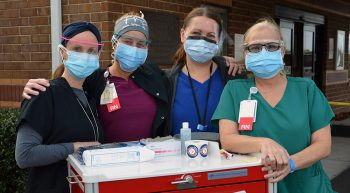 Four nurses with mobile vaccination unit