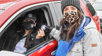 Woman in mask hands badge to woman in car wearing mask
