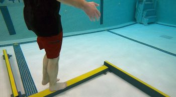 Man walking on balance beam in pool