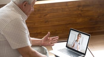 Man talking to doctor on laptop