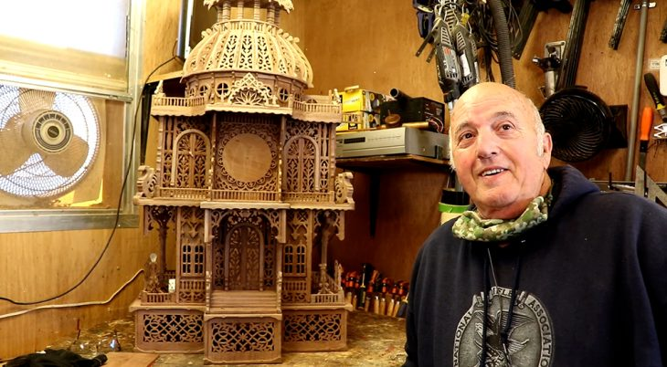Man with wood carving of clock dome