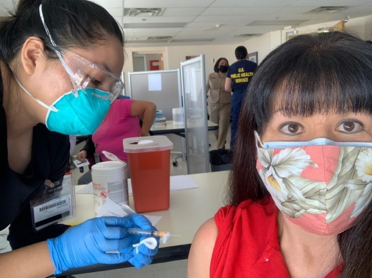 Theresa Clay (right), a member of Navajo Nation, receives her COVID-19 vaccine booster shot from a nurse with the Indian Health Service (IHS), Shayla Jim, during a recent IHS vaccination event in Albuquerque.