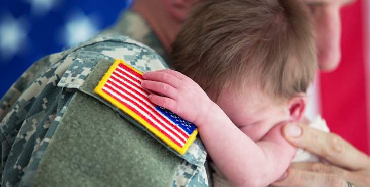 military family holding baby
