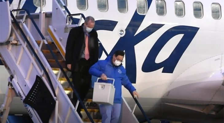 Man carrying vaccines down airplane stairs