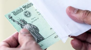 Hands pulling a government check out of an envelope