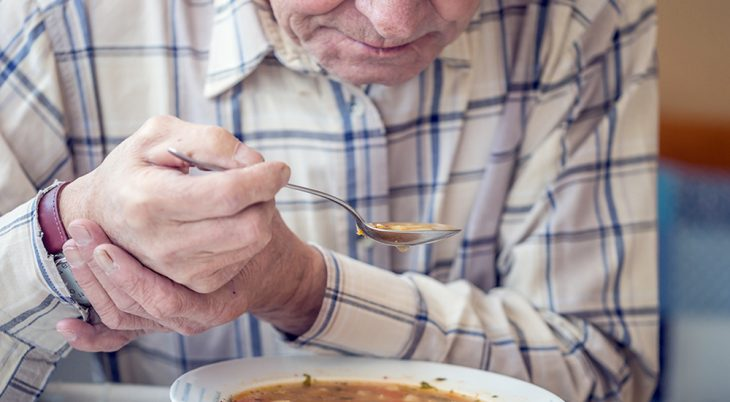 Elderly man with holds spoon in both hands as he eats soup.
