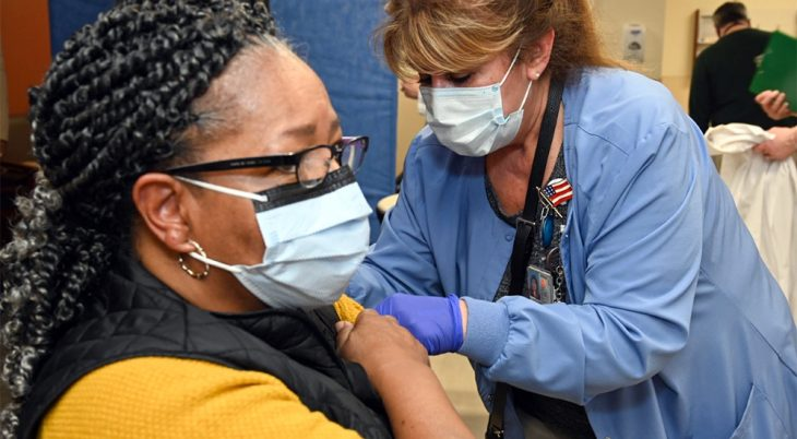 A health care worker gives an injection to a woman patient