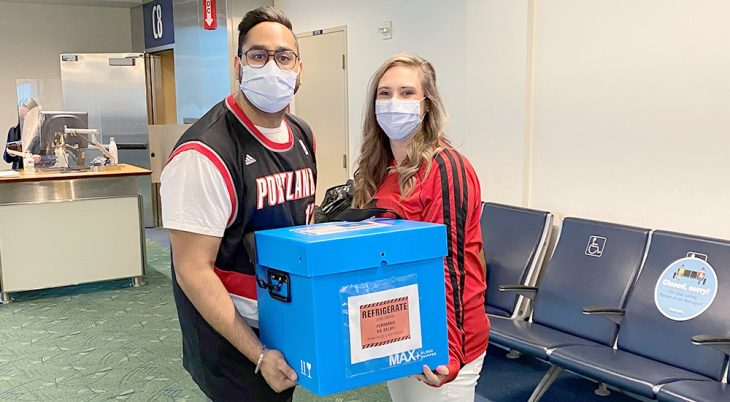 Man and woman holding refrigerated vaccines