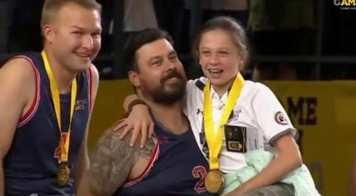 Man and daughter holding medals at THIS event