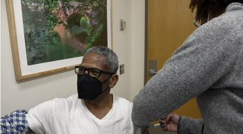 Man wearing mask receiving vaccine