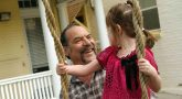 Man and his daughter who is in a swing
