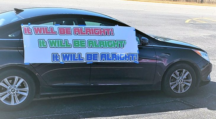 Car with IT WILL BE ALL RIGHT sign