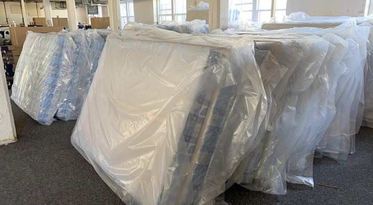 New mattresses stacked up in large room