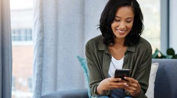Smiling woman reading cell phone
