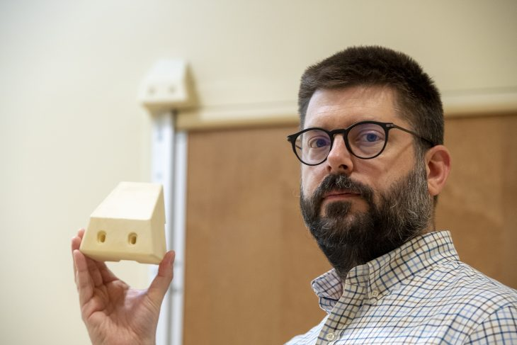 Frank Moore, the suicide prevention coordinator at VA Pittsburgh, displays the 3D block that was installed on all of the bathroom doors in patient rooms in the facility's mental health wing to prevent a potential hanging. (Photo by Bill George)