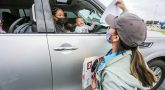 Woman holding up sign for smiling baby in car
