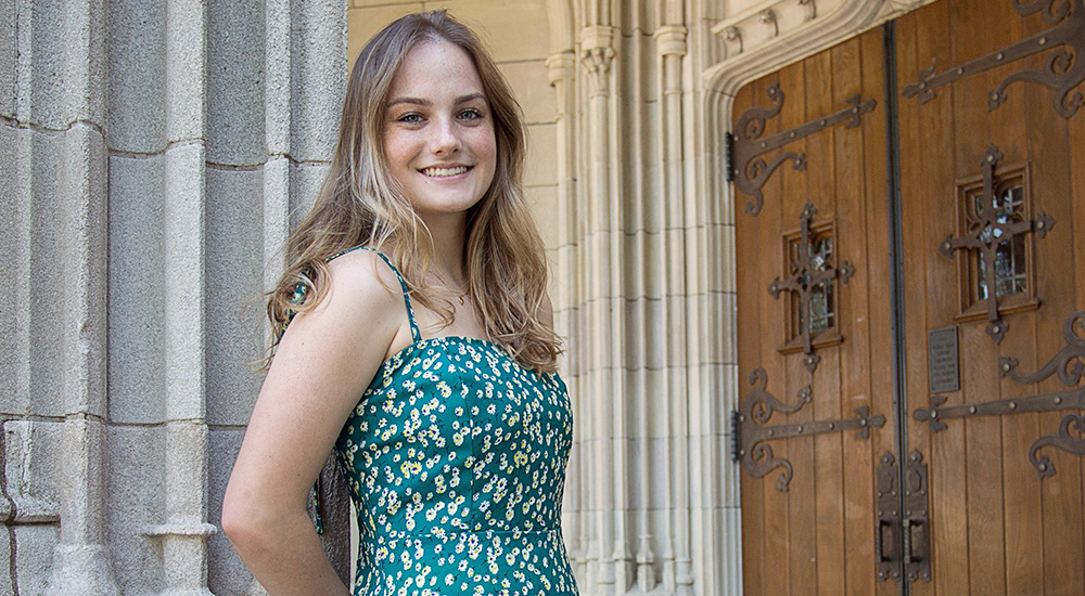 Photo of smiling young woman at university door