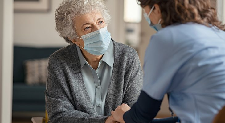 n elderly patient and health care worker sit facing each other with clasped hands.