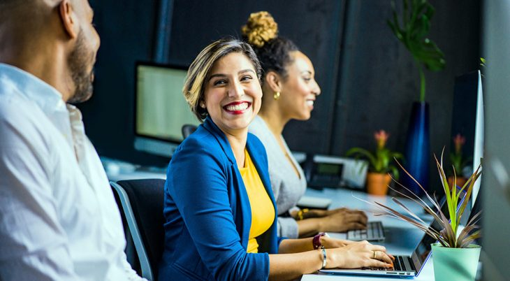 Three smiling employees at workstations