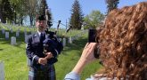 A videographer films Air Force Master Sgt. Adam Tianello, a bagpiper with the Ceremonial Brass, during a video shoot April 26 at Culpeper National Cemetery in Virginia.