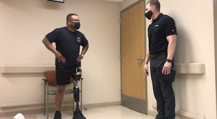 Man with prosthetic leg talks with trainer