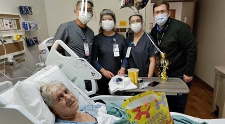 Four people at a Veterans' hospital bedside