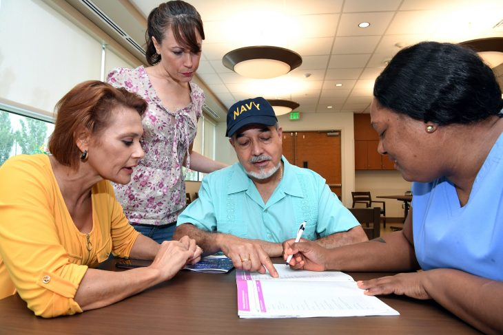 A family discusses the Resource Guide with a nurse.