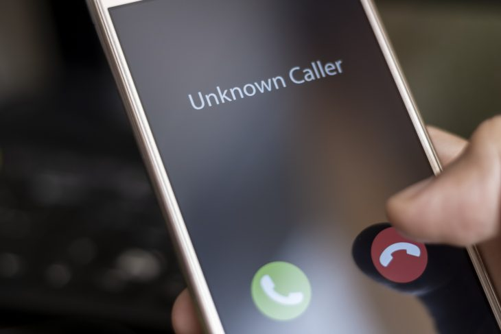 A man holds a phone in his hand with a call from an unknown number.