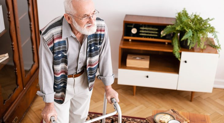 Senior handicap man walking in the apartment leaning on a walker