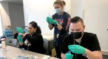 Three clinical staff members prepare vaccines