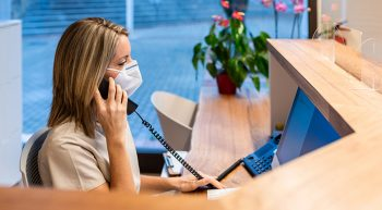 Woman wearing mask on the phone in workstation.