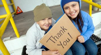 Two homeless children holding Thank You sign