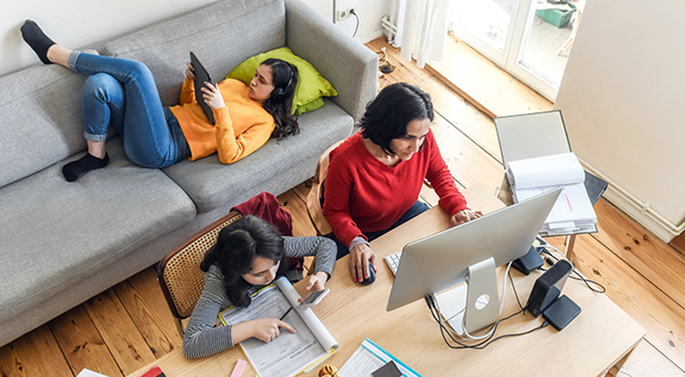 Woman working on laptop while children do homework
