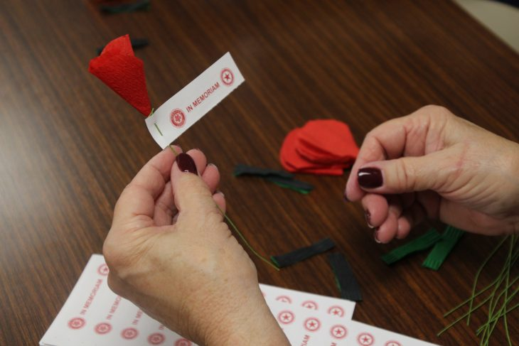 person holding red poppy paper flower